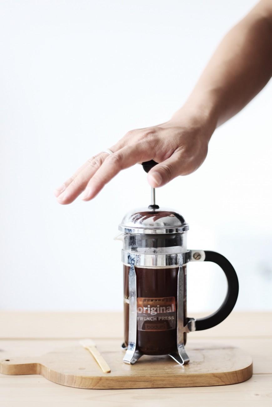 12. Chờ thêm 4 phút. Sau đó, từ từ ấn nhẹ (press) để đẩy lượng cà phê xuống đáy bình thông qua màng lọc. Lúc này chỉ còn nước cà phê ở phía trên.